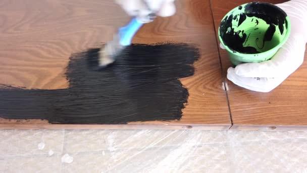 junge Frau bemalt braunes Holzbrett schwarz mit Pinsel. Nahaufnahme.
