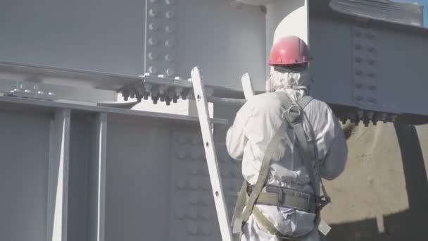 der Arbeiter im Schutzanzug malt mit weißer Farbe die Baukonstruktionen.