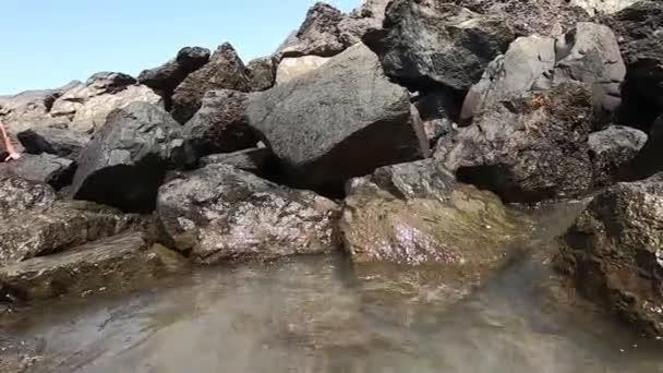 Nagy kövek elrendezve a parton. Sáros hullámok.