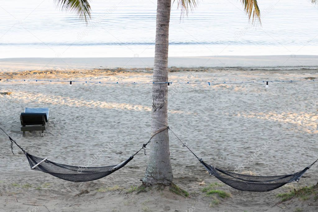 Two twin hammocks hanging from coconut tree on beach