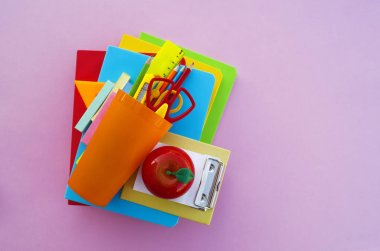 The schoolboy's accessories lie on a pink table. Textbooks and office. Back to school.