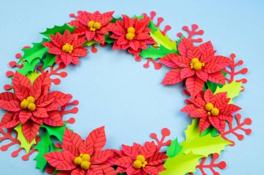 Christmas wreath of paper flowers poinsettia. Favorite hobby is manual work. Green holly and red berries. Blue background.