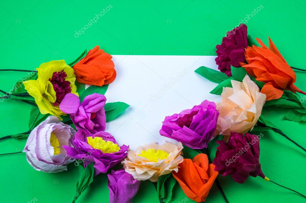Utensils and tools for making crepe paper flowers on green background. Cosmos flower bouquet