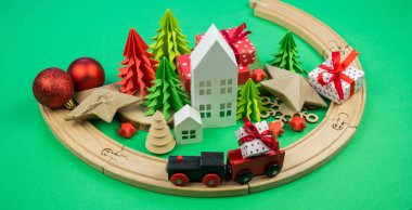 A toy wooden train carries a box with a gift to the child. Christmas magic city. Paper tree and star, decoration for the holiday. New Year's toy.