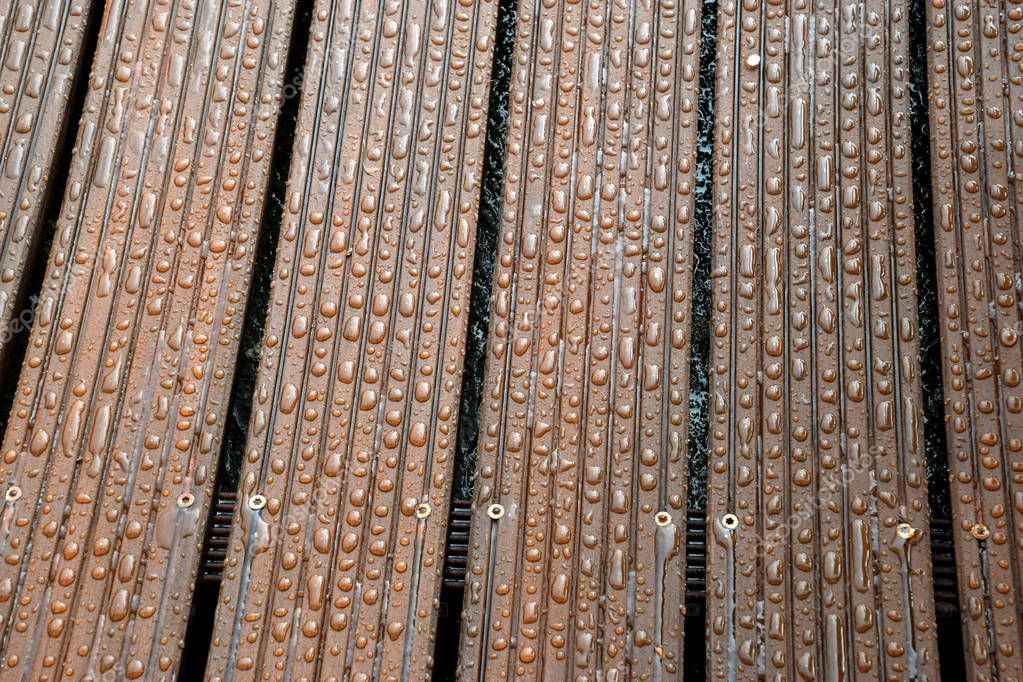 outdoor wooden terrace after a rain with small drops of water on them, impregnated wood lets water drip off and does not allow dirt to adhere