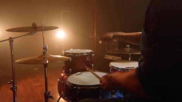 férfi dobos, a paradiddle lecke a piros dob és a kék pergődob, a próbateremben, alacsony fény