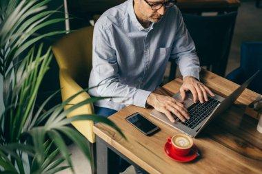 Top view of man using laptop on coffee break in restaurant