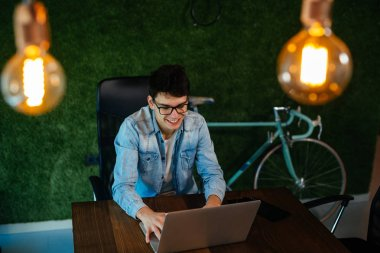 Young man software developer using laptop in modern office