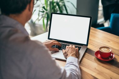Man working online with laptop and drinking coffee