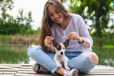 woman playing with her puppy on river dock