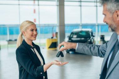 salesman giving car keys to customer in car showroom