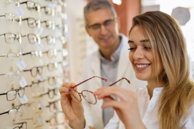 woman choosing best glasses with. optician in the background