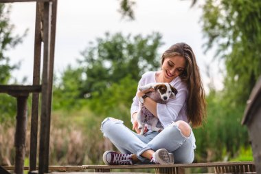 woman playing with her puppy outdoor