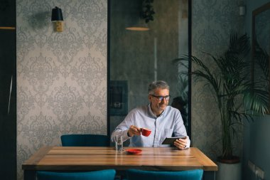 Grey haired businessman using tablet and drinking coffee in cafeteria