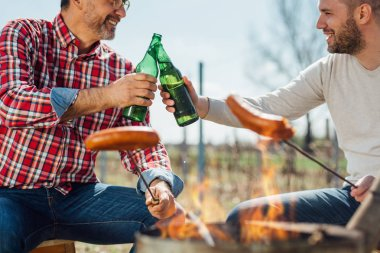 Party time outdoor, men clinking beer bottles cooking sausages on grill.