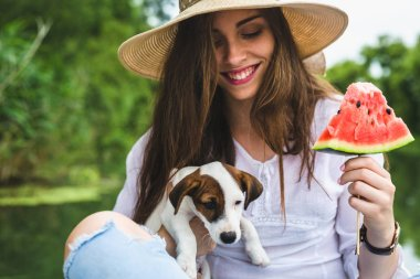 beautiful woman enjoying day with her puppy by the river