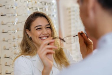 Female optician helping male customer to find best eyeglasses in store