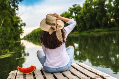 woman sitting on river dock