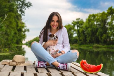 woman enjoying summer days with her puppy , sitting on the river dock