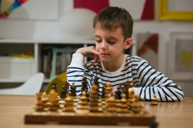 boy in striped jumper playing chess