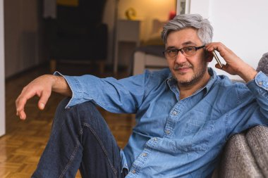 Gray haired man using smartphone at home