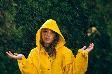 Girl in yellow raincoat having fun in the rain