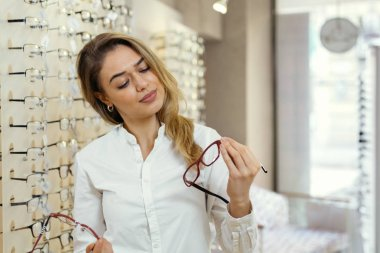 Pretty young woman choosing glasses in optic store.