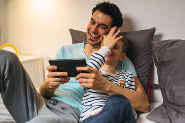 family time together. father and son using tablet at home