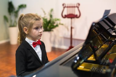 Pretty little girl learning playing piano