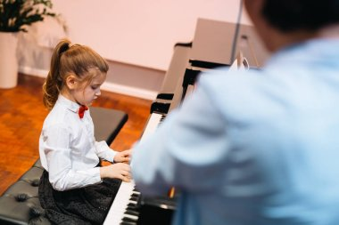 little girl playing piano with professor assistance