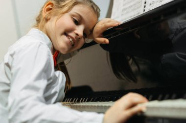 little girl daydreaming over concert piano