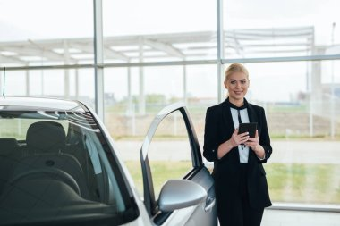 sell agent in car showroom holding tablet