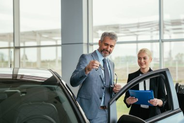 car sell agent with client in car showroom