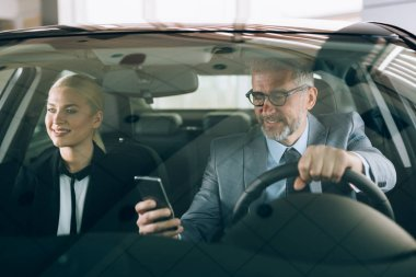 man using smartphone while driving car