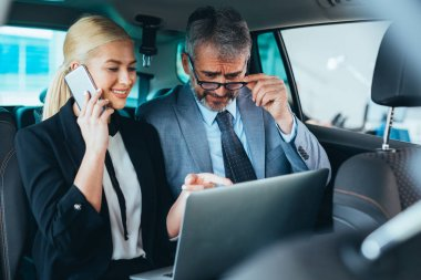 business colleagues using laptop sitting backseat of car