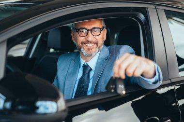senior man well dressed sitting in car and holding car keys in car showroom