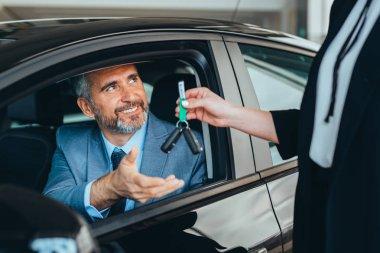 saleswoman giving car keys to customer in car dealership showroom