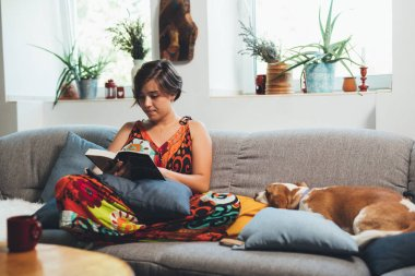 woman relaxed in sofa reading book at her home