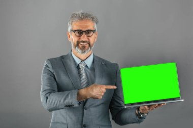 studio shot of business man holding laptop computer with green screen