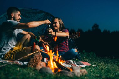 romantic couple on night camping, playing guitar and barbecue sausages on camping fire