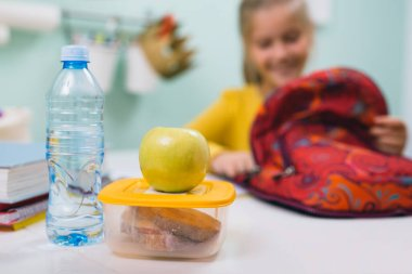 schoolgirl packing her school bag and preparing school snack