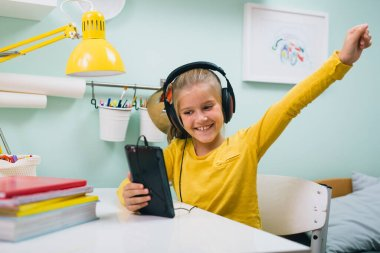 girl using tablet listening music on headphones sitting table in her room