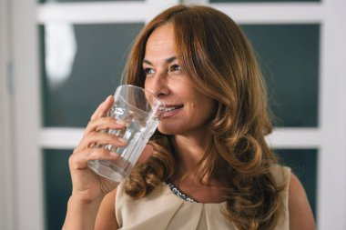 portrait of mature woman holding glass of water