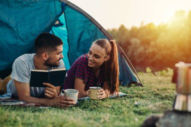 romantic couple on camping laying in tent and reading book