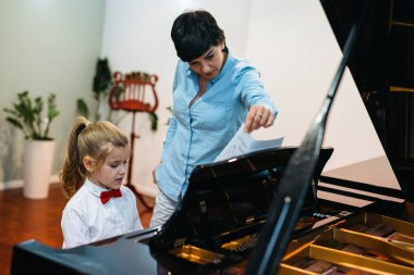 little girl playing piano her professor assistance