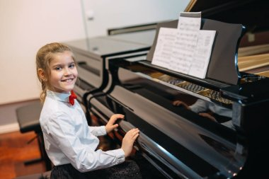 happy little girl teaching to play piano