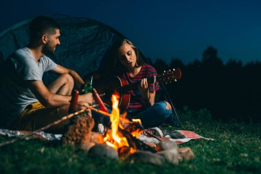 romantic couple playing guitar while camping outdoor by the camping fire. night scene