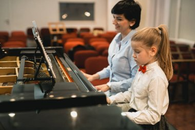 little girl practicing playing piano with her professor assistance