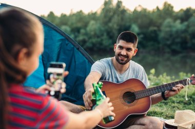 romantic couple on camping together having fun outdoor by the lake