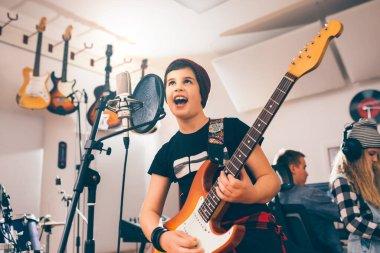 boy playing guitar in music studio